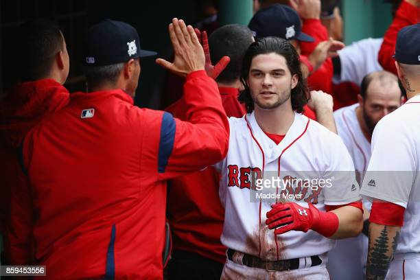 Andrew Benintendi of the Boston Red Sox celebrates with teammates in the dugout after hitting a tworun home run in the fifth inning against the...