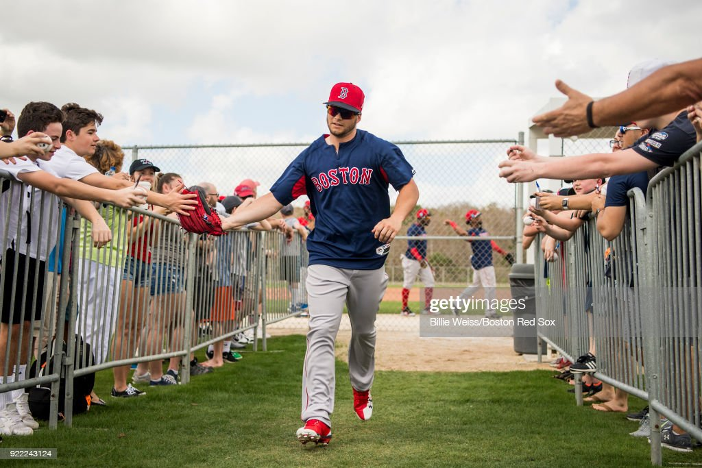 Andrew Benintendi #16 of the Boston Red Sox high fives fans during a team workout on February 21, 2018 at jetBlue Park at Fenway South in Fort Myers, Florida .