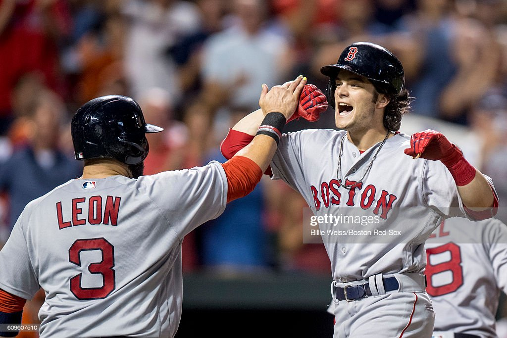 Andrew Benintendi #40 of the Boston Red Sox high fives Sandy leon #3 after hitting a three run home run during the sixth inning of a game against the Baltimore Orioles on September 21, 2016 at Oriole Park at Camden Yards in Baltimore, Maryland.