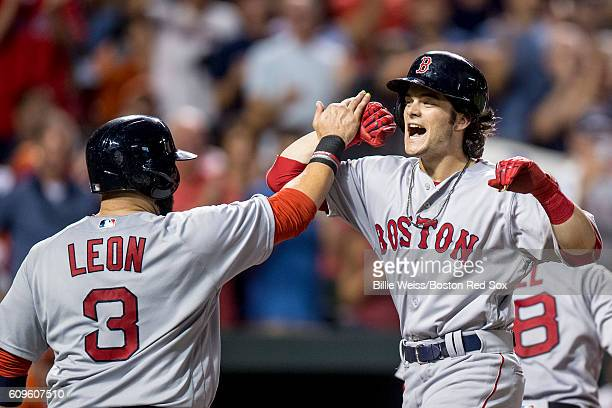 Andrew Benintendi of the Boston Red Sox high fives Sandy leon after hitting a three run home run during the sixth inning of a game against the...