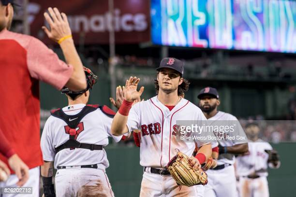 Andrew Benintendi of the Boston Red Sox high fives teammates after a victory against the Chicago White Sox on August 3 2017 at Fenway Park in Boston...
