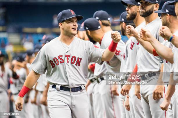 Andrew Benintendi of the Boston Red Sox high fives teammates as he is introduced before the Opening Day game against the Tampa Bay Rays on March 29...
