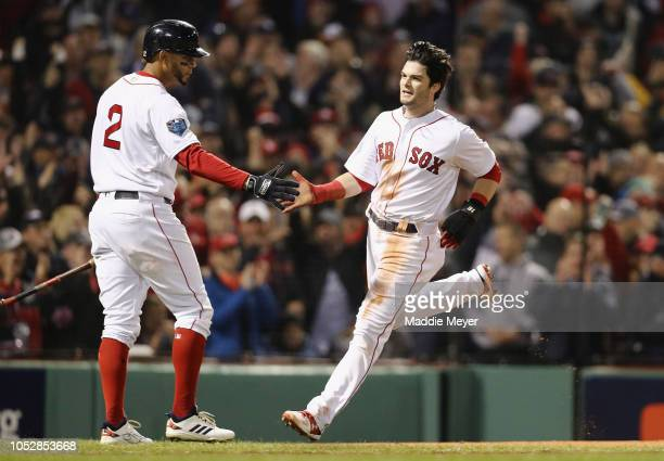 Andrew Benintendi of the Boston Red Sox is congratulated by his teammate Xander Bogaerts after scoring a first inning run against the Los Angeles...