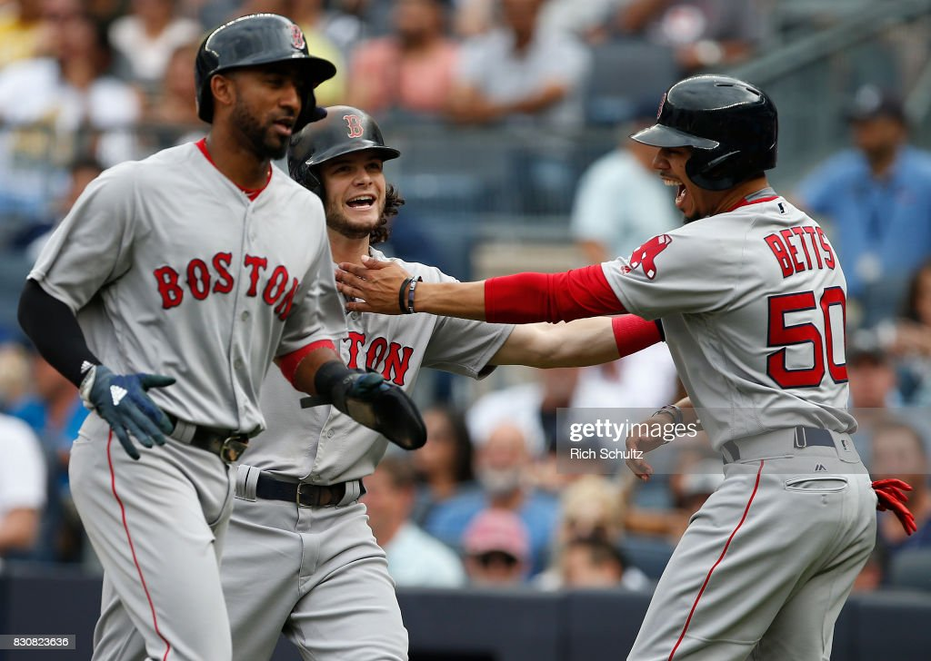 Andrew Benintendi #16 of the Boston Red Sox is congratulated by teammates Eduardo Nunez #36 and Mookie Betts #50 after all three scored on Benintendi's three- home run against the New York Yankees during the third inning of a game at Yankee Stadium on August 12, 2017 in the Bronx borough of New York City.