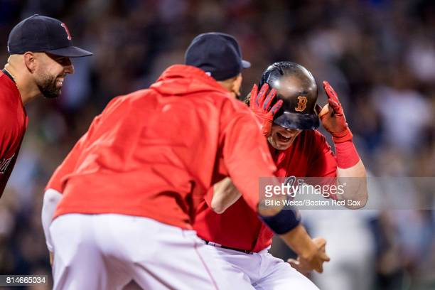 Andrew Benintendi of the Boston Red Sox is mobbed by teammates after being walked to drive in the game winning run during the ninth inning of a game...