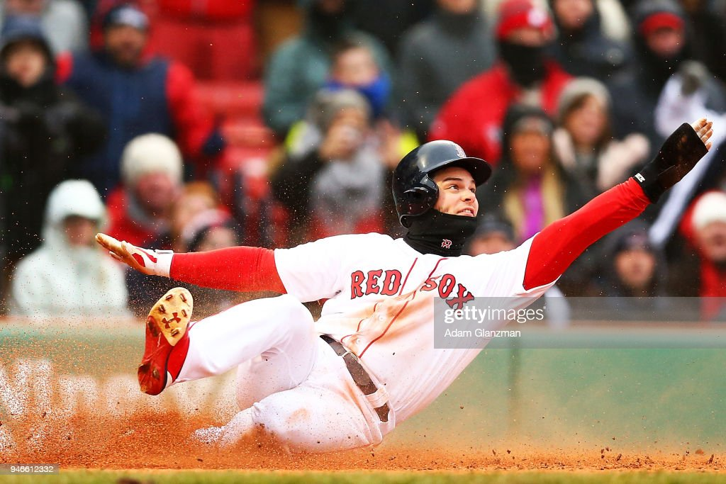 Andrew Benintendi #16 of the Boston Red Sox is tagged out at home plate by Caleb Joseph #36 of the Baltimore Orioles in the seventh inning of a game at Fenway Park on April 15, 2018 in Boston, Massachusetts. All players are wearing #42 in honor of Jackie Robinson Day.