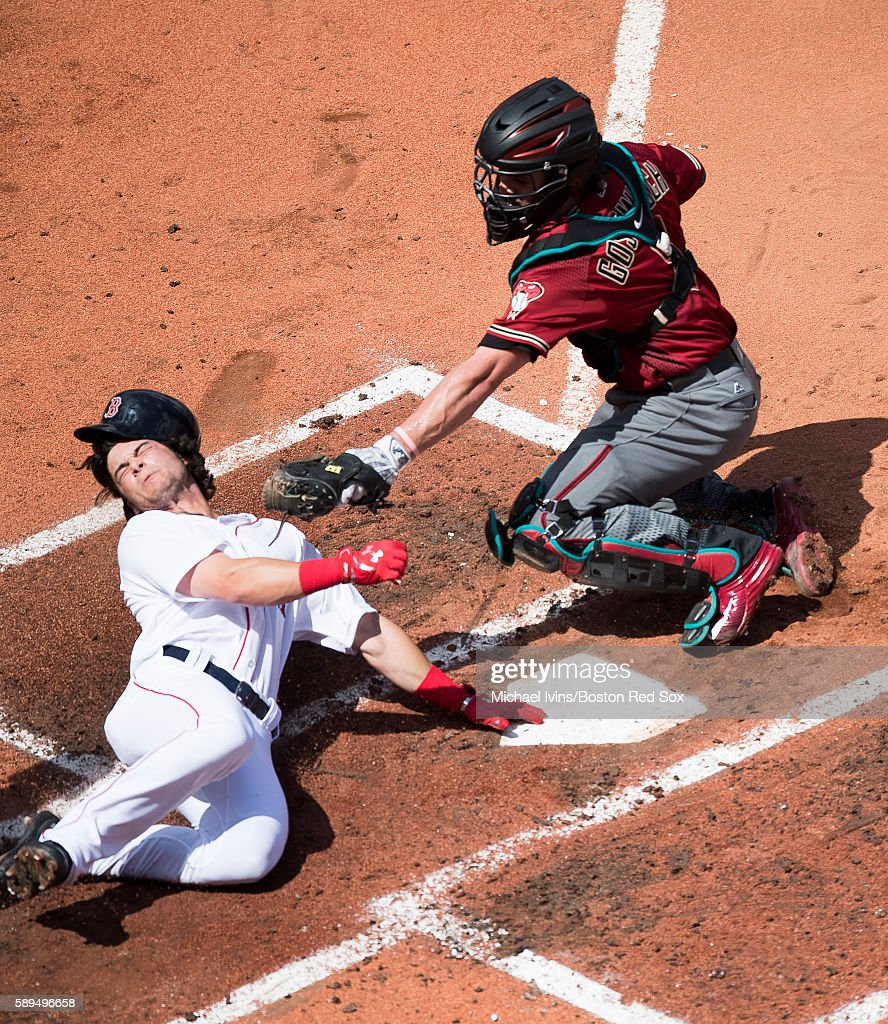 Andrew Benintendi #40 of the Boston Red Sox is tagged out at the plate by Tuffy Gosewisch #8 of the Arizona Diamondbacks in the second inning on August 14, 2016 at Fenway Park in Boston, Massachusetts.