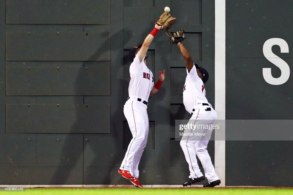 Andrew Benintendi #16 of the Boston Red Sox jumps over Jackie Bradley Jr. #19 to catch a double hit by Randal Grichuk #15 of the Toronto Blue Jays during the fourth inning at Fenway Park on September 13, 2018 in Boston, Massachusetts.