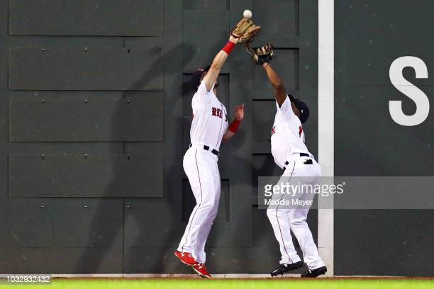 Andrew Benintendi of the Boston Red Sox jumps over Jackie Bradley Jr #19 to catch a double hit by Randal Grichuk of the Toronto Blue Jays during the...