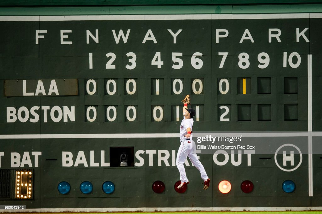 Andrew Benintendi #16 of the Boston Red Sox leaps as he catches a line drive in front of the Green Monster scoreboard during the eighth inning of a game against the Los Angeles Angels of Anaheim on June 28, 2018 at Fenway Park in Boston, Massachusetts.