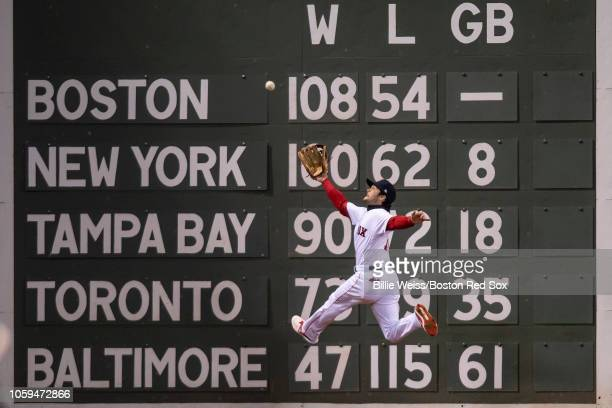 Andrew Benintendi of the Boston Red Sox makes a leaping catch against the wall on a ball hit by Brian Dozier of the Los Angeles Dodgers during the...