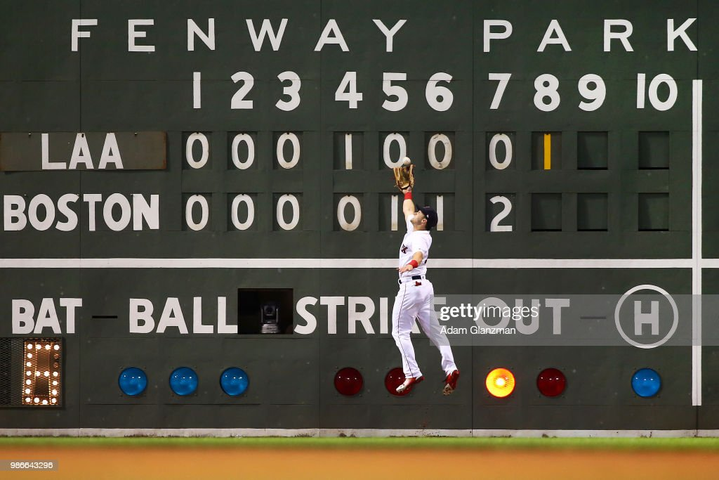 Andrew Benintendi #16 of the Boston Red Sox makes a leaping catch on the warning track in the eighth inning of a game against the Los Angeles Angels at Fenway Park on June 28, 2018 in Boston, Massachusetts.
