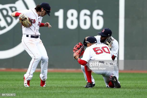 Andrew Benintendi of the Boston Red Sox Mookie Betts and Jackie Bradley Jr #19 celebrate after defeating the Oakland Athletics 62 at Fenway Park on...
