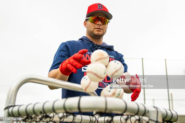 Andrew Benintendi of the Boston Red Sox puts balls in the basket during a team workout on March 5 2019 at JetBlue Park at Fenway South in Fort Myers...