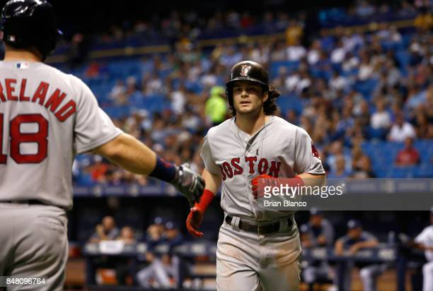 Andrew Benintendi of the Boston Red Sox runs in to celebrate with Mitch Moreland after scoring off of an RBI single by Mookie Betts during the sixth...