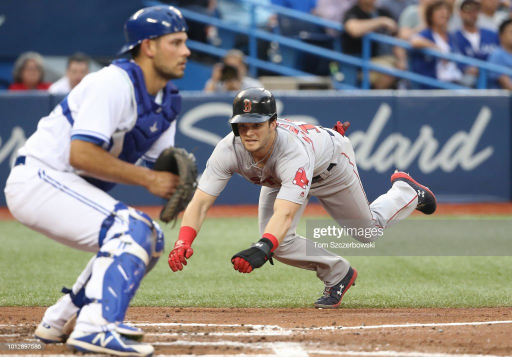 Andrew Benintendi #16 of the Boston Red Sox slides home to score a run on an RBI single by J.D. Martinezin the fourth inning during MLB game action against the Toronto Blue Jays at Rogers Centre on August 7, 2018 in Toronto, Canada.
