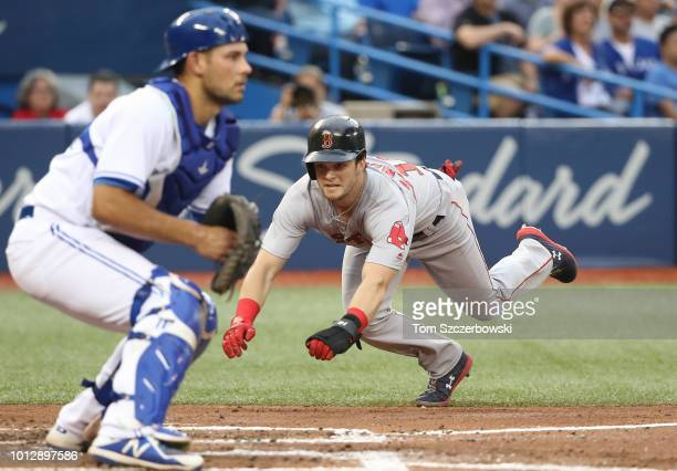 Andrew Benintendi of the Boston Red Sox slides home to score a run on an RBI single by JD Martinezin the fourth inning during MLB game action against...