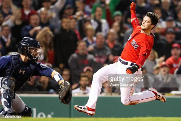 Andrew Benintendi of the Boston Red Sox slides safely into home plate past Tom Murphy of the Seattle Mariners to score in the fifth inning at Fenway...