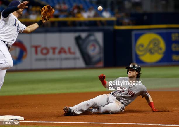 Andrew Benintendi of the Boston Red Sox steals third base ahead of third baseman Evan Longoria of the Tampa Bay Rays during the sixth inning of a...