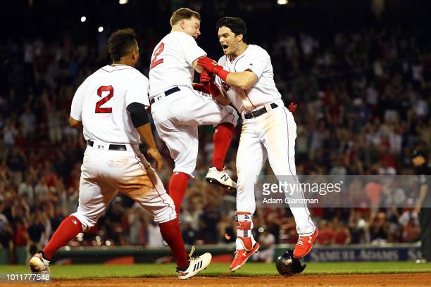 Andrew Benintendi reacts with Brock Holt and Xander Bogaerts of the Boston Red Sox after hitting the gamewinning walkoff single to defeat the New...