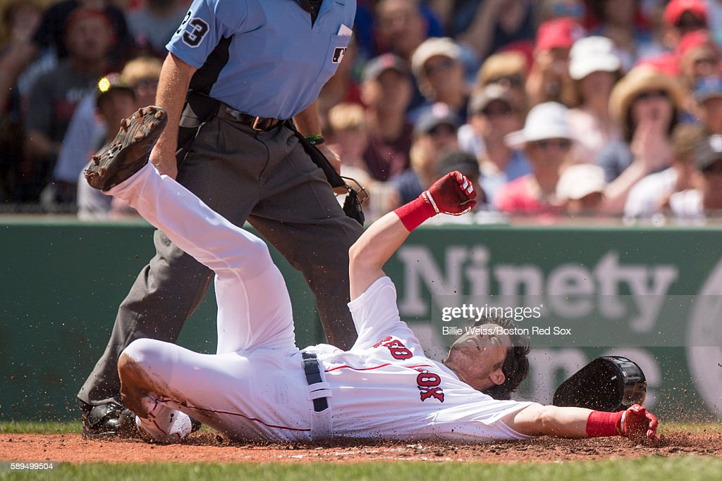 Andrew Benitendi #40 of the Boston Red Sox is tagged out as he slides into home during the second inning of a game against the Arizona Diamondbacks on August 14, 2016 at Fenway Park in Boston, Massachusetts.
