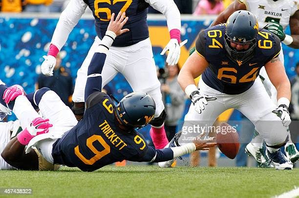 Andrew Billings of the Baylor Bears sacks Clint Trickett of the West Virginia Mountaineers causing a fumble as Mark Glowinski looks for the ball in...
