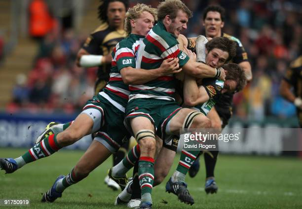 Andrew Bishop of the Ospreys is tackled by Tom Croft and Billy Twelvetrees and Johne Murphy during the Heineken Cup match between Leicester Tigers...