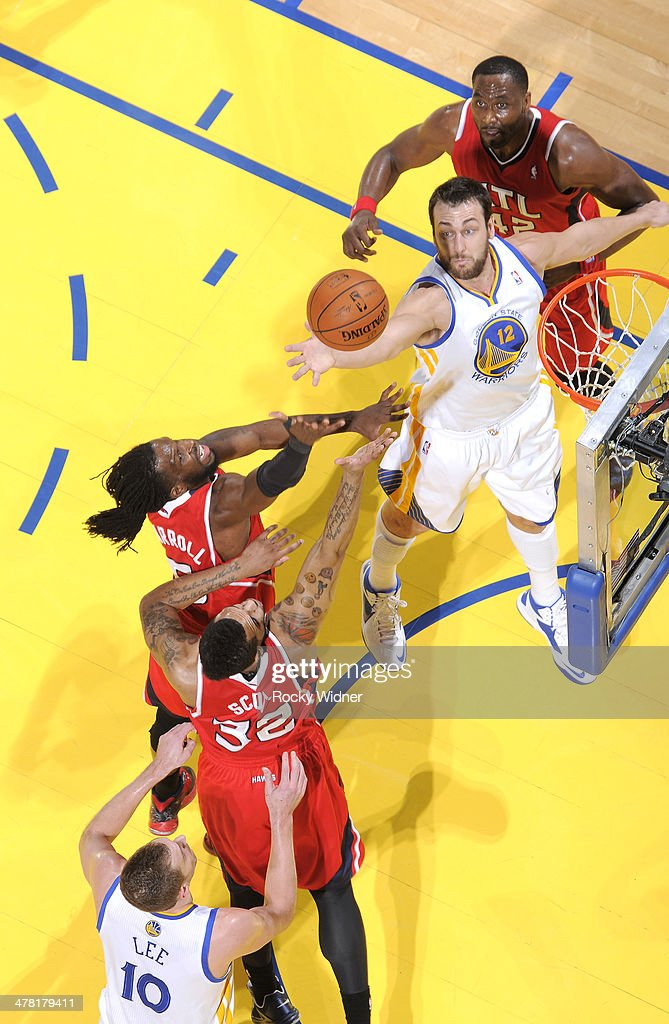 Andrew Bogut #12 of the Golden State Warriors reaches for the rebound against the Atlanta Hawks on March 7, 2014 at Oracle Arena in Oakland, California.