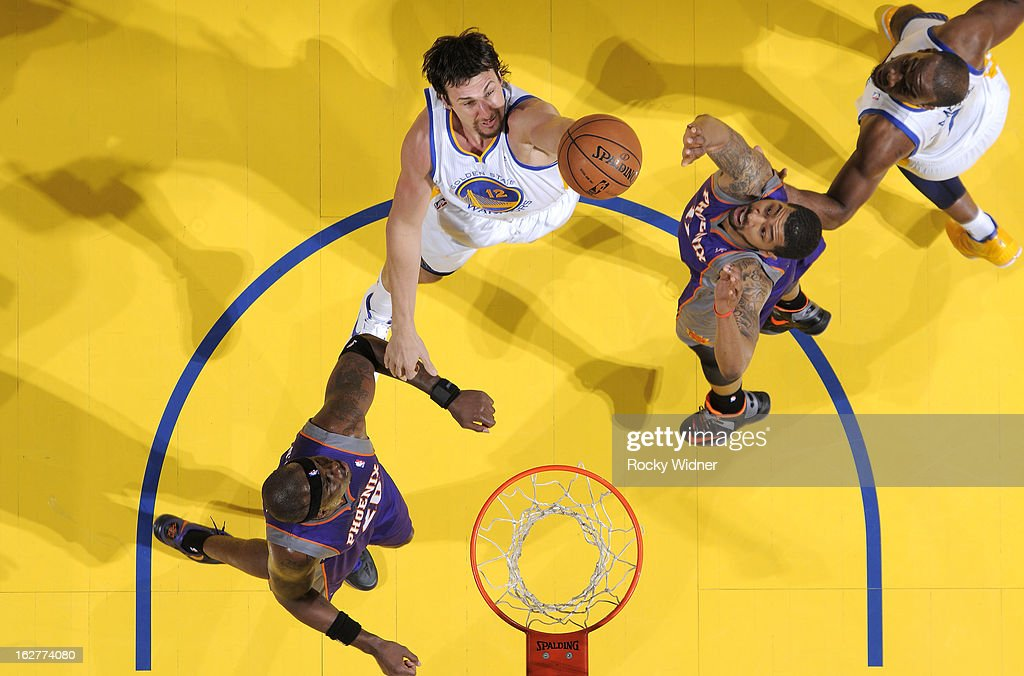 Andrew Bogut #12 of the Golden State Warriors shoots against Jermaine O'Neal #20 and Markieff Morris #11 of the Phoenix Suns on February 20, 2013 at Oracle Arena in Oakland, California.