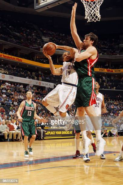 Andrew Bogut of the Milwaukee Bucks blocks against DJ Augustin of the Charlotte Bobcats on April 2 2010 at the Time Warner Cable Arena in Charlotte...