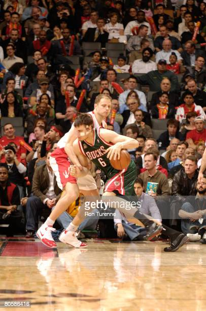 Andrew Bogut of the Milwaukee Bucks drives on Rasho Nesterovic of the Toronto Raptors on April 9 2008 at the Air Canada Centre in Toronto Canada NOTE...