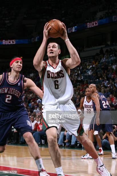 Andrew Bogut of the Milwaukee Bucks drives to the lane against Josh Boone of the New Jersey Nets at the Bradley Center December 29 2007 in Milwaukee...