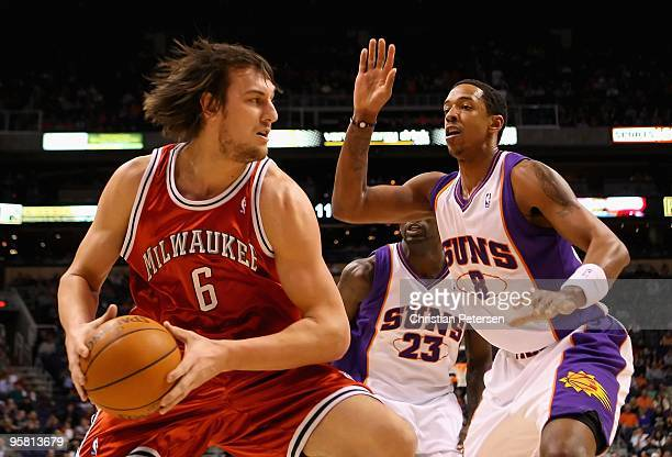Andrew Bogut of the Milwaukee Bucks handles the ball under pressure from Channing Frye of the Phoenix Suns during the NBA game at US Airways Center...