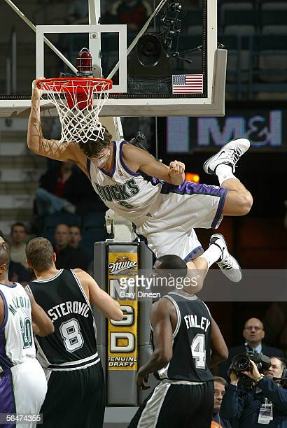 Andrew Bogut of the Milwaukee Bucks hangs from the rim after a dunk as Rasho Nesterovic and Michael Finley of the San Antonio Spurs look on on...
