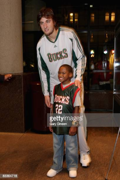 Andrew Bogut of the Milwaukee Bucks poses with a young fan before the preseason game against the Detroit Pistons on October 11 2008 at the Bradley...