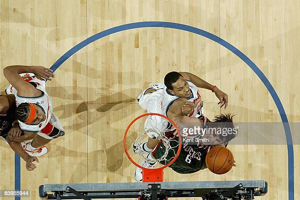 Andrew Bogut of the Milwaukee Bucks puts a shot up over Ryan Hollins and Jared Dudley of the Charlotte Bobcats during the game on November 22 2008 at...