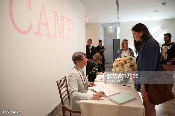 Andrew Bolton autographs copies of the Camp Notes on Fashion exhibition catalogue at Metropolitan Museum of Art on September 04 2019 in New York City