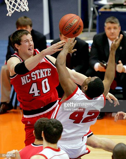 Andrew Brackman of the North Carolina State Wolfpack and Alando Tucker of the Wisconsin Badgers fight for a rebound during their regional semi-final...