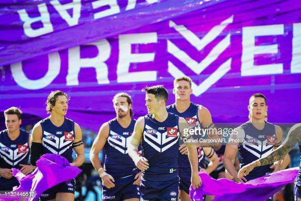 Andrew Brayshaw of the Dockers breaks the banner during the 2019 AFL round 01 match between the Fremantle Dockers and the North Melbourne Kangaroos...