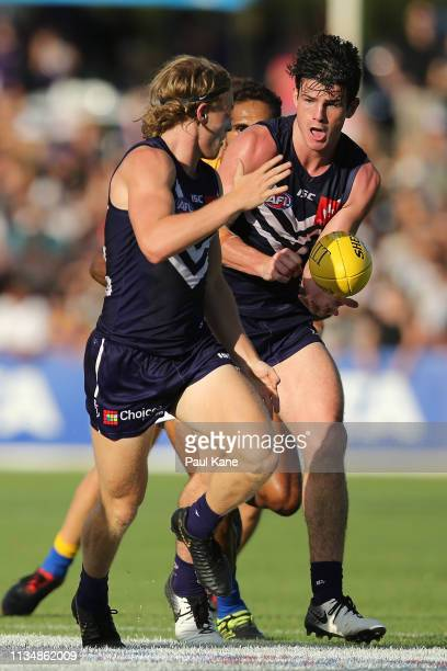 Andrew Brayshaw of the Dockers handballs to Stefan Giro during the 2019 JLT Community Series AFL match between the Fremantle Dockers and the West...