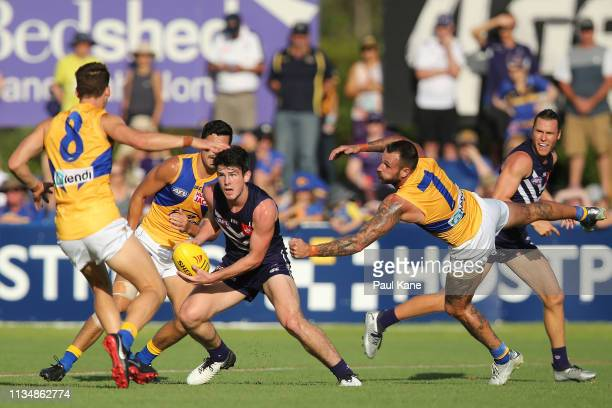 Andrew Brayshaw of the Dockers slips a tackle by Chris Masten of the Eagles during the 2019 JLT Community Series AFL match between the Fremantle...