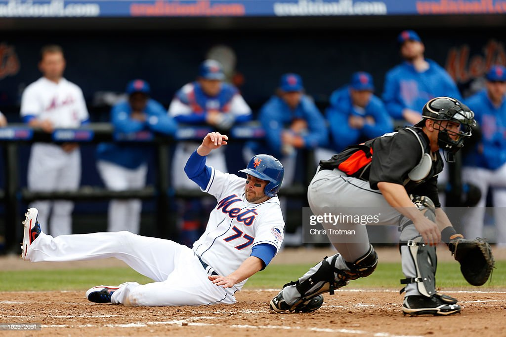 Andrew Brown #77 of the New York Mets slides in to home plate past Rob Brantly #19 of the Miami Marlins at Tradition Field on March 2, 2013 in Port St. Lucie, Florida.