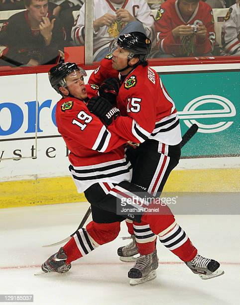 Andrew Brunette of the Chicago Blackhawks collides with teammate Jonathan Toews duing a game against the Winnipeg Jets at the United Center on...