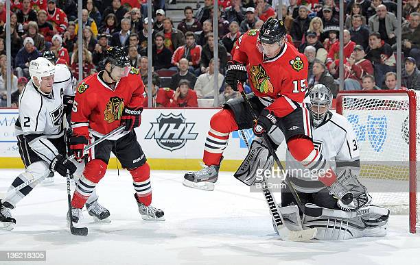 Andrew Brunette of the Chicago Blackhawks jumps in front of Los Angeles Kings goalie Jonathan Quick to avoid the puck as Steve Montador of the...