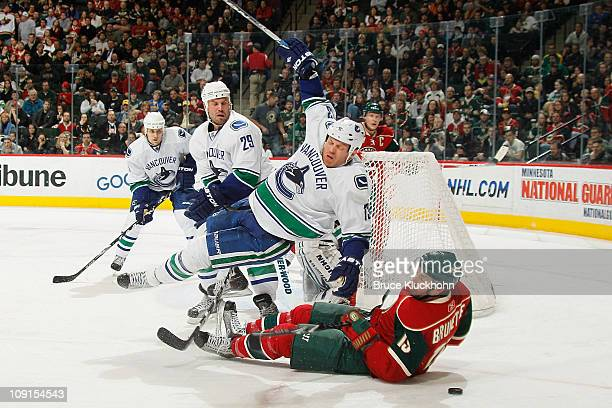 Andrew Brunette of the Minnesota Wild and Raffi Torres of the Vancouver Canucks fall to the ice while battling for the puck during the game at Xcel...