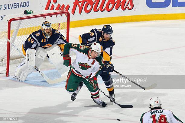 Andrew Brunette of the Minnesota Wild handles the puck against Henrik Tallinder of Buffalo Sabres at HSBC Arena on March 12 2010 in Buffalo New York