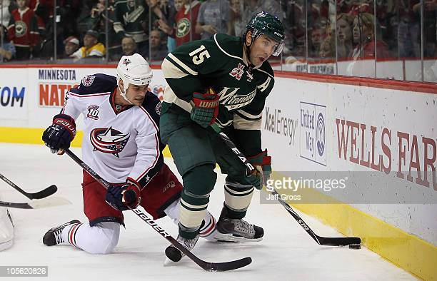 Andrew Brunette of the Minnesota Wild is pursued by Rostislav Klesla of the Columbus Blue Jackets for the puck during the third period at Xcel Energy...