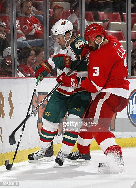 Andrew Brunette of the Minnesota Wild tries to control the puck while taking a check by Andreas Lilja of the Detroit Red Wings on March 11 2010 at...