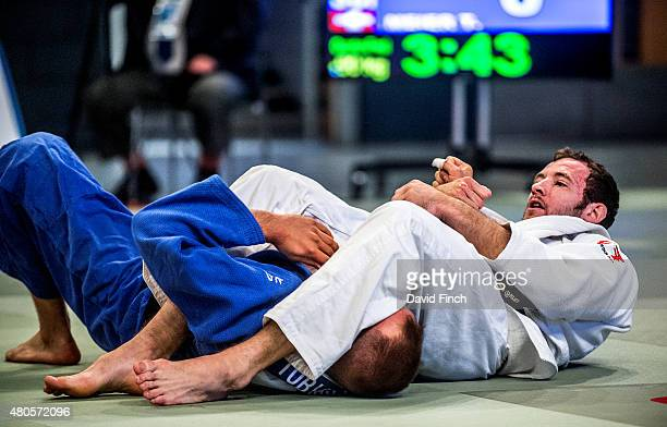 Andrew Burns of Great Britain armlocks Tobias Meier of Switzerland into submission to win the contest by an iippon as he progressed to the u90kg...