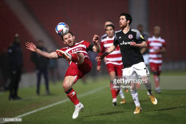 Andrew Butler of Doncaster Rovers is put under pressure by Paul Smyth of Accrington Stanley during the Sky Bet League One match between Doncaster...